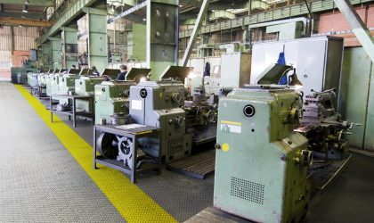 Row of green metal lathes in factory.